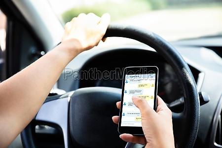 frau sitzt in auto typing textnachricht