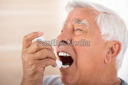 man using asthma inhaler