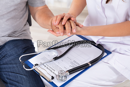 doctor holding senior patients hand