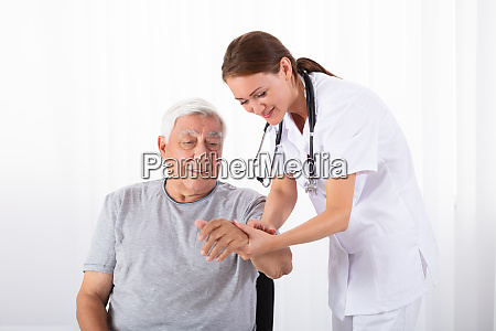 doctor examining male patients pulse