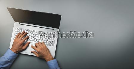 man typing on laptop computer top