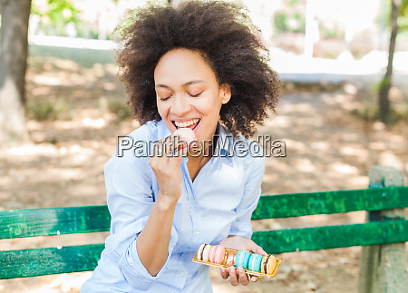 young african woman eating macarons cookie