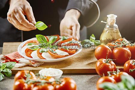 chef making a fresh caprese salad