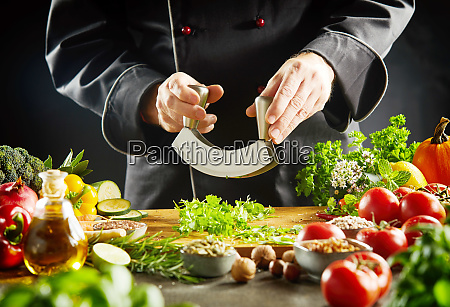 chef using a mezzaluna knife to