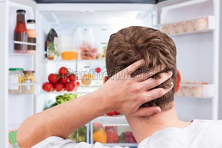 confused man looking at food in
