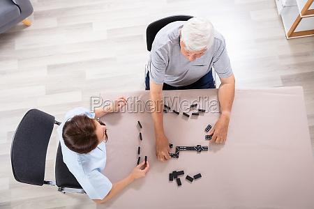 hausmeister und senior man spielen dominosteine