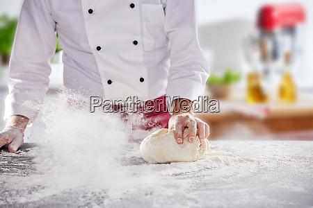 chef rollt teig in weissem mehl