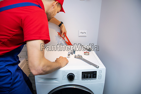 plumber installing washing machine in domestic