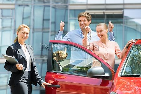 dealer standing besides couple holding key