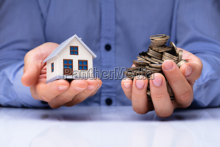 man holding house model and coins