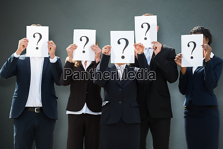 businesspeople hiding their faces behind question