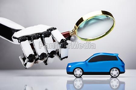 robot examining blue car