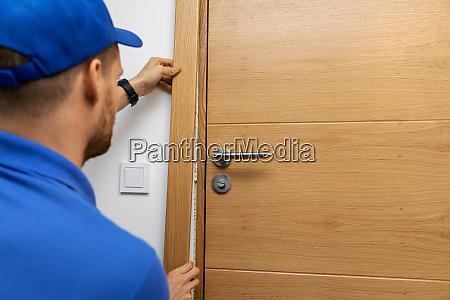 man installing door architrave