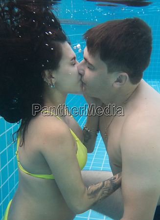 pregnant couple relaxing in the pool