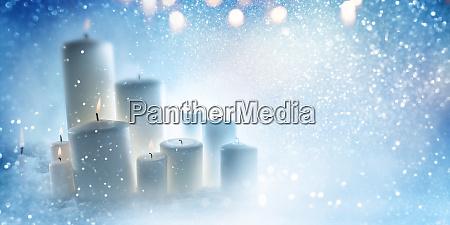 kerzen im blauem kalten schneebedeckten winter