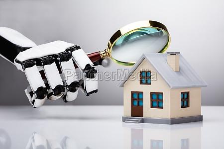 robotic hand examining house model