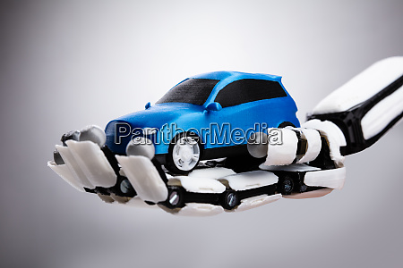 robotic hand holding blue car