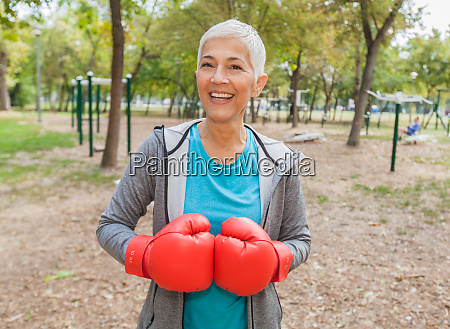 healthy senior woman with boxing glove