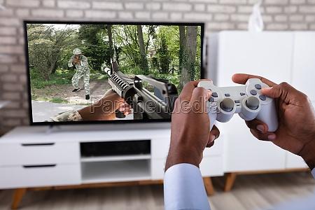 mann spielt actionspiel im fernsehen