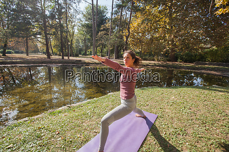 woman practicing yoga exercise at city
