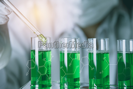 researcher with glass laboratory chemical test