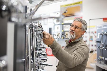 senior man choosing a bathroomkitchen tap