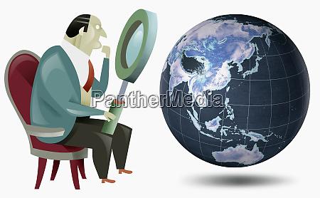 geschaeftsmann schaut mit lupe auf globus