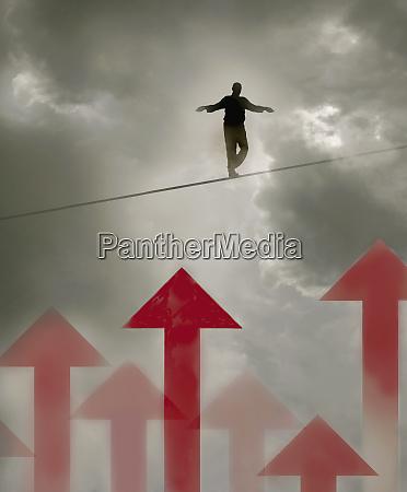 man walking tightrope over arrows in