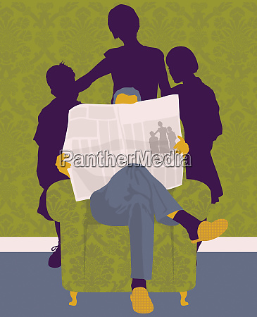 family standing behind man reading newspaper