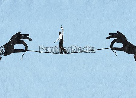 businessman walking tightrope on string between