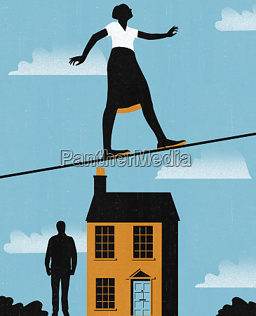 businesswoman on tightrope above house and