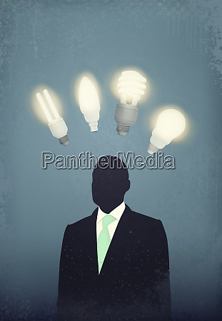 businessman with cfl light bulbs over