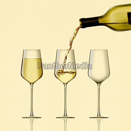 white wine being poured into three
