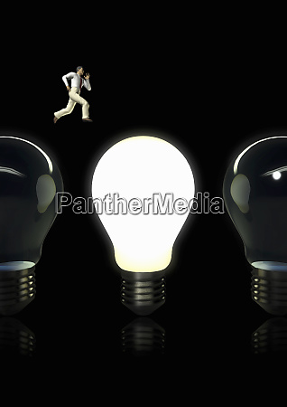 businessman jumping from dark light bulb