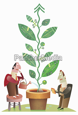 businessmen watering growing green technology plant