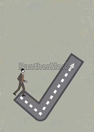 businessman walking up check mark path