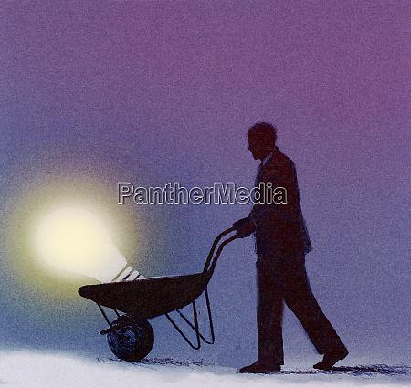 businessman pushing light bulb in wheelbarrow
