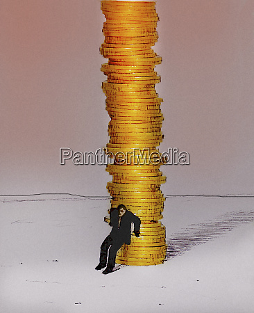businessman protecting large pile of money