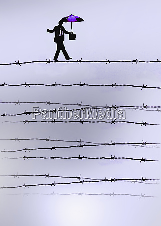 businessman walking barbed wire tightrope