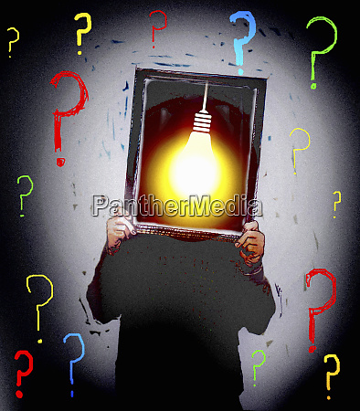 man surrounded by question marks holding