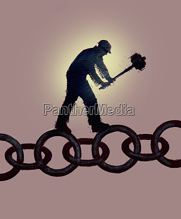 workman breaking chain with sledgehammer