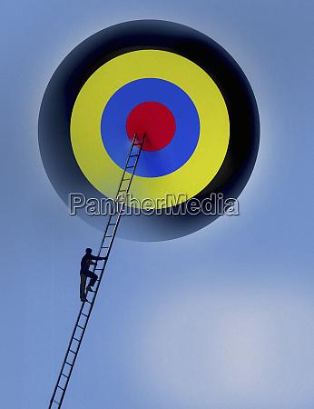 man climbing ladder towards bulls eye