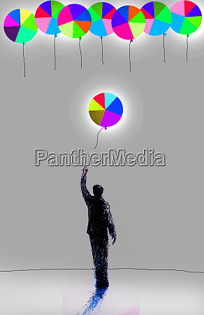 businessman releasing pie chart balloon
