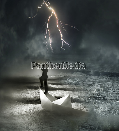 businessman in sinking paper boat at
