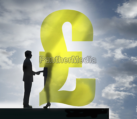 businessman and businesswoman shaking hands behind