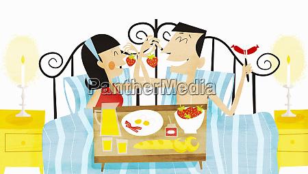 glueckliches paar essen fruehstueck im bett