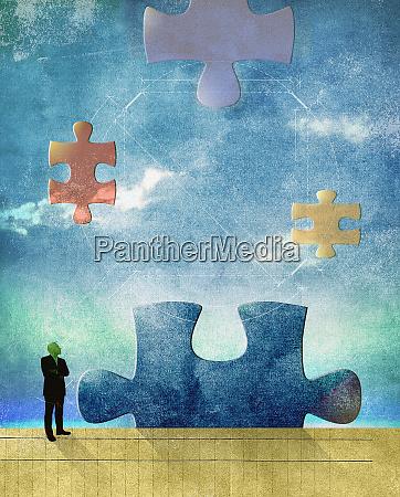 man contemplating large jigsaw puzzle pieces