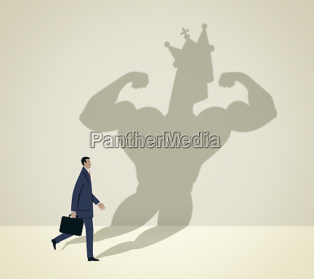 businessman walking casting muscular shadow wearing