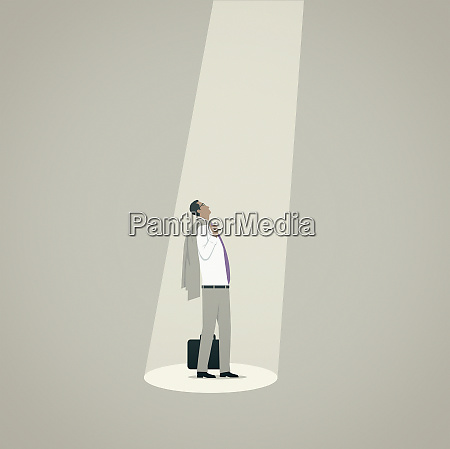 businessman looking up standing in spotlight