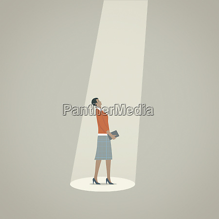 businesswoman looking up standing in spotlight